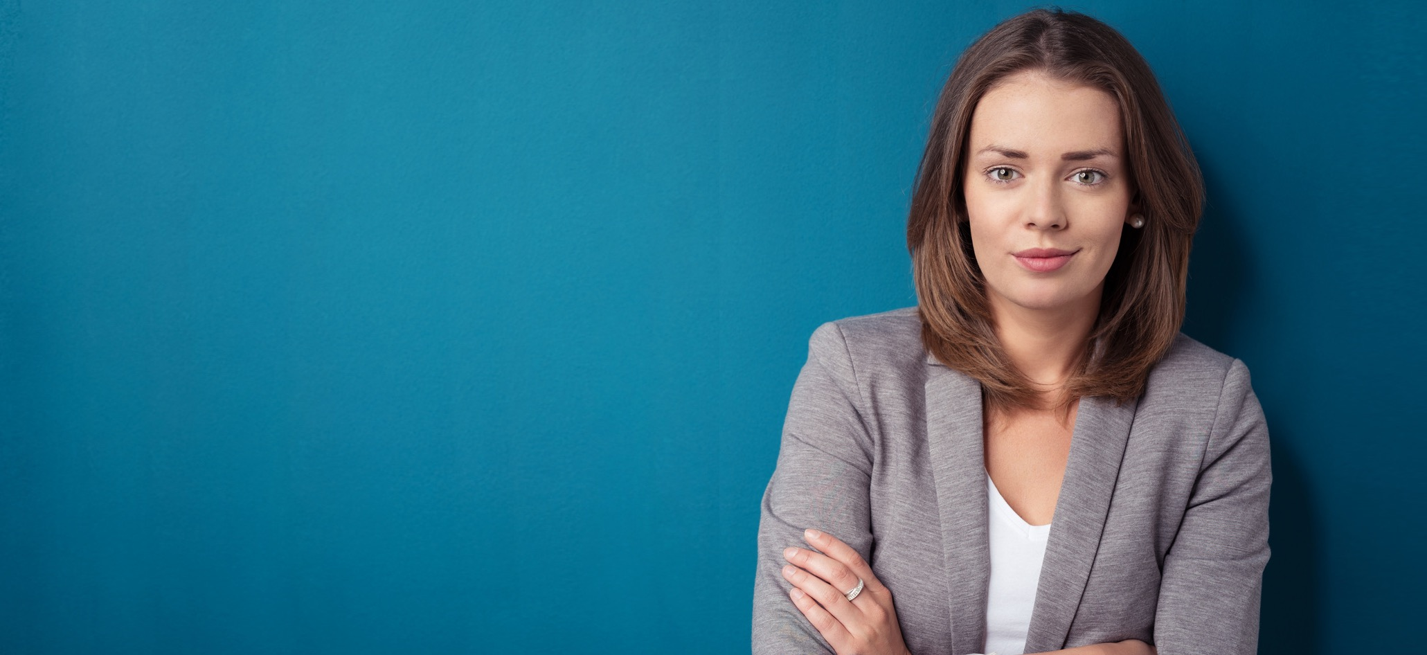 geschäftsfrau mit verschränkten armen vor blauem hintergrund