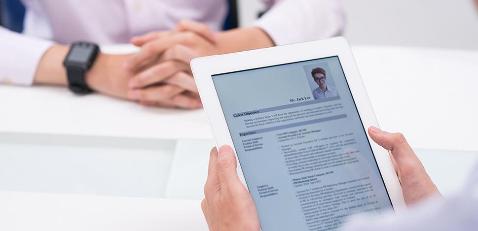 Une personne tient une tablette numérique avec un CV