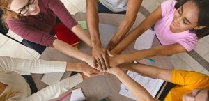 Multiracial teenagers joining hands together in cooperation, preparing common academic project, top view